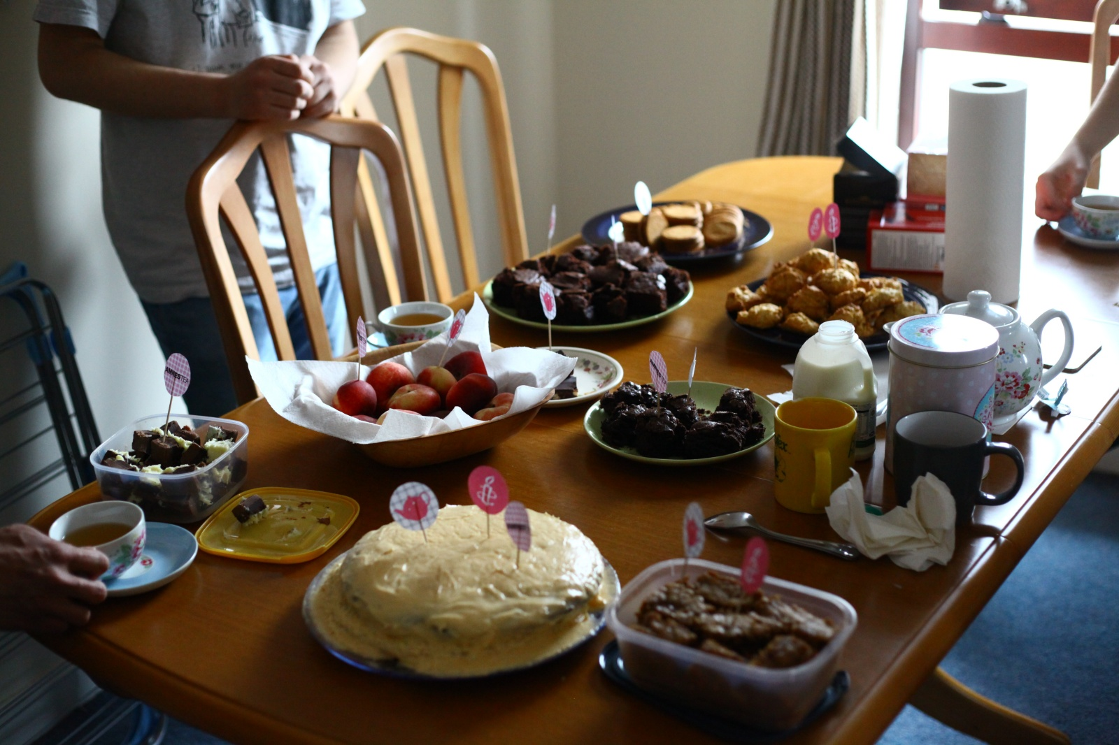 A table *full* of cakes biscuits sweets and tea!